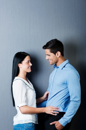 next to each other: Beautiful young couple in love standing next to each other and looking into each others eyes, isolated on blue background. Stock Photo