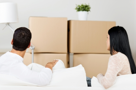moving out: Stressed out couple sitting on the sofa and looking at moving boxes