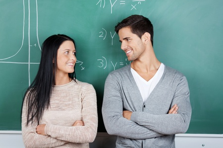 Happy male and female students with arms crossed looking at each other against chalkboard photo