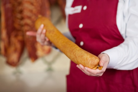 Midsection of female butcher holding sausage in shop photo