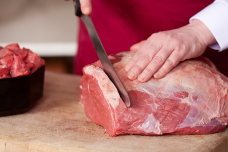 Closeup of the hands of a butcher cutting slices of raw meat off a large loin Zdjęcie Seryjne