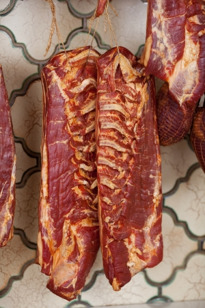 unhealthful: Closeup of pieces of meat hanging in shop Stock Photo