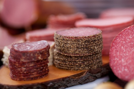 butcher shop: Selection of different sliced salami on a wooden board in a counter display at a butchery