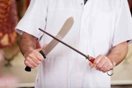 carniceria: Sección media de hombre que afila el cuchillo de carnicero en la tienda