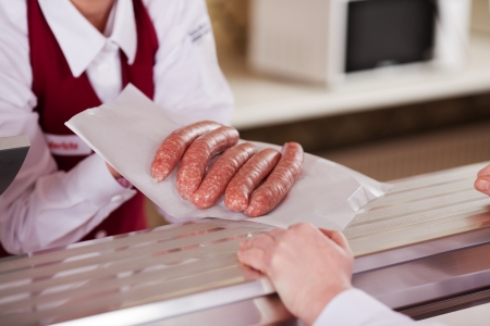 displaying: Midsection of butcher displaying sausages in front of customer at shop counter