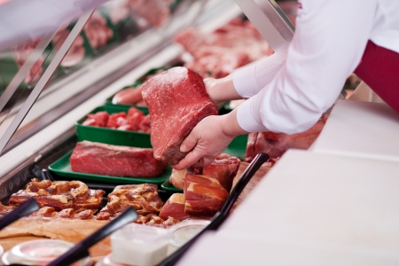 refrigerated: saleswoman offering fresh meat at display in supermarket Stock Photo
