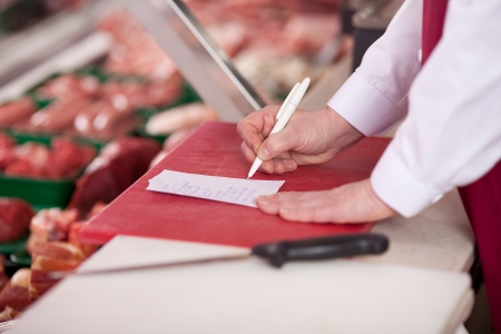 meat counter: Butchers hand writing on paper at counter in shop