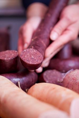 charcutería: Primer de las manos de carnicero celebración de la salchicha en la tienda Foto de archivo