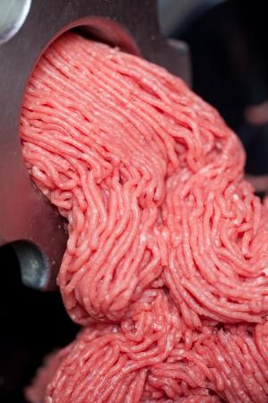 ショップでグラインダーから出てくるひき肉のクローズ アップ
