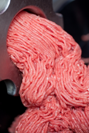 processing: Closeup of minced meat coming out from grinder in shop Stock Photo