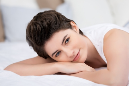 unwinding: Smiling young female relaxing on the bed and looking at camera. Stock Photo