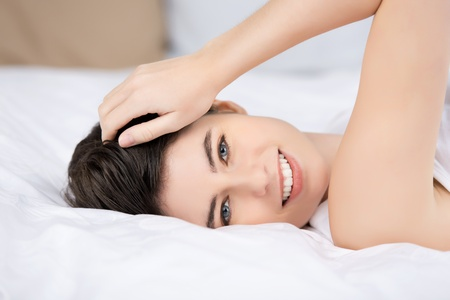 Closeup portrait of happy young woman lying on bed at home photo