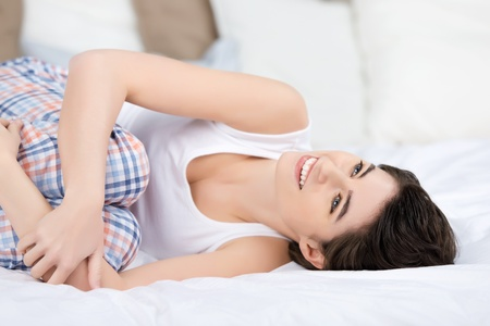 hugging knees: Happy young woman looking away while hugging knees in bed at home Stock Photo