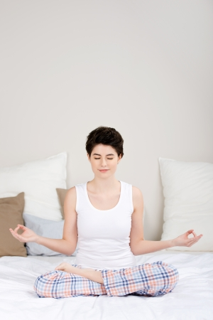 Full length of young woman meditating in lotus position on bed photo