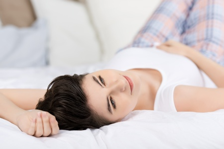 Young woman relaxing on bed and thinking about something.
