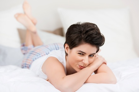 naughty woman: Beautiful young woman relaxing in bed and giving a naughty smile. Stock Photo