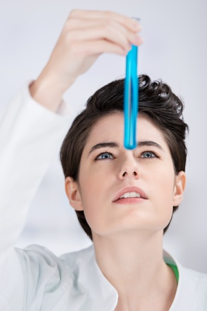 technologist: Beautfiul young laboratory technician testing a substance holding a test tube filled with a blue chemical solution up in front of her face as she watches for a reaction