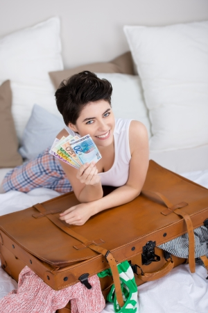 Beautiful smiling woman showing Euros while lying on the bed with a suitcase. photo