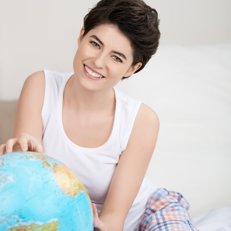 Portrait of happy young woman searching for travel destination on globe at home photo