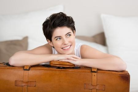 mujer con maleta: Mujer joven feliz mirando a otro lado mientras se inclina en la maleta en casa