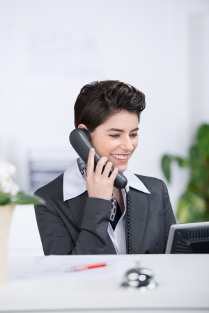 calling: Happy receptionist conversing on landline phone at counter Stock Photo