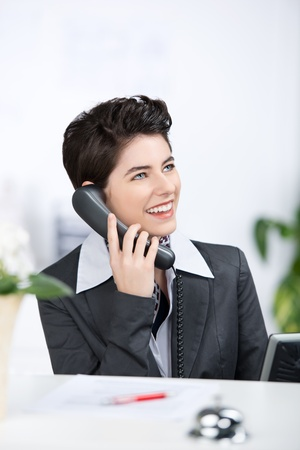 A charming female business executive sitting on her desk, smiling and talking on phone. photo