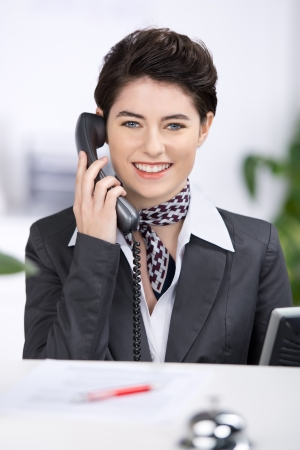neckcloth: Beautiful stylish young female receptionist with a friendly smile talking on a telephone