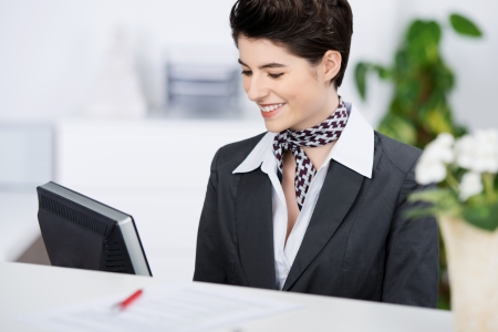 Happy young receptionist smiling while using computer at counter photo