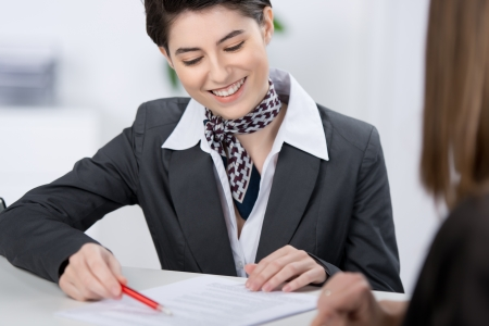 relaciones publicas: Joven con estilo hermosa representante de servicios al cliente que explica un documento a un cliente con una encantadora sonrisa