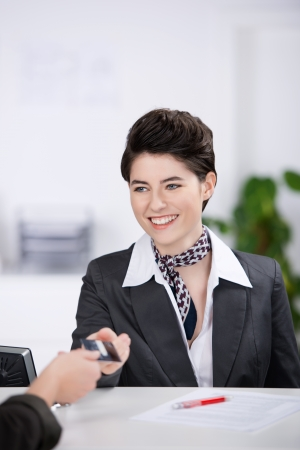 Happy young receptionist giving cardkey to customer at reception photo