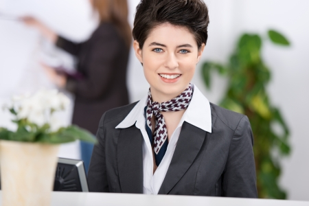 Amazingly beautiful female well dressed receptionist welcoming the guests with a charming smile. photo