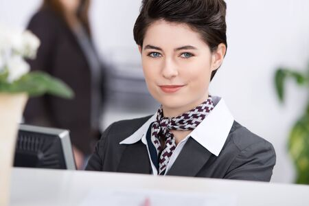 Closeup portrait of confident young receptionist at reception photo