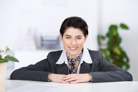reception counter: Beautiful stylish young female receptionist with a welcoming smile leaning her arms on the top of a counter as she waits to greet clients Stock Photo