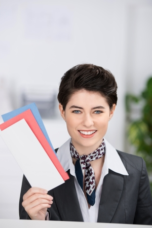 Happy young receptionist holding traveling documents at counter photo