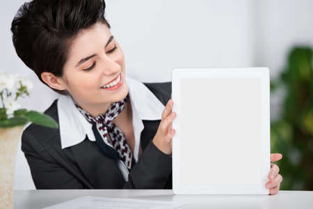 Pretty stylish young receptionist showing a blank tablet screen to the camera balancing it on top of the counter and looking at the screen with a smile photo