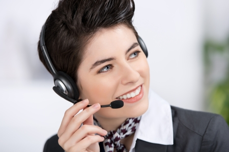 Closeup of happy young female customer service executive conversing on headset in office photo