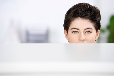 hides: Closeup of young businesswoman looking at camera in cubicle at office
