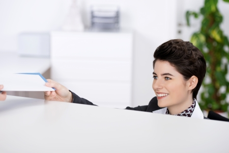 hotel receptionist: Happy young receptionist giving traveling documents at reception counter Stock Photo
