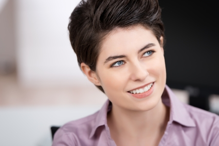 creative thinking: Closeup of thoughtful young businesswoman looking away while smiling in office Stock Photo