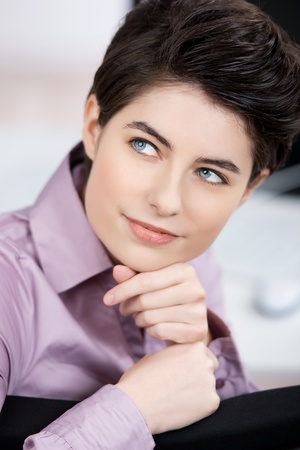 Closeup of thoughtful young businesswoman looking away in office photo