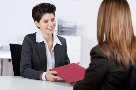 interview job: Feliz candidata mujer joven que da el archivo a la empresaria en el escritorio en la oficina Foto de archivo