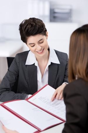 cv: Felice giovane candidata donna spiegando il suo CV in colloquio di lavoro