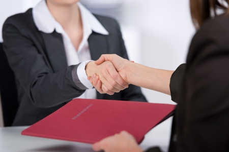 여성 후보는 사무실에서 책상에 사업가 손을 흔들면서