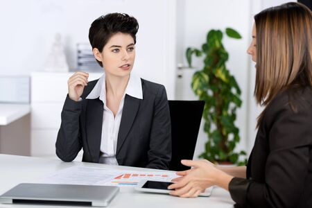Businesswomen discussing in meeting at desk in office photo