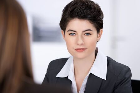 Portrait of confident businesswoman with coworker in foreground in office photo