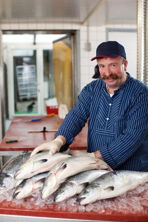 visboer: lachende man verkoop zalm op de vismarkt Stockfoto