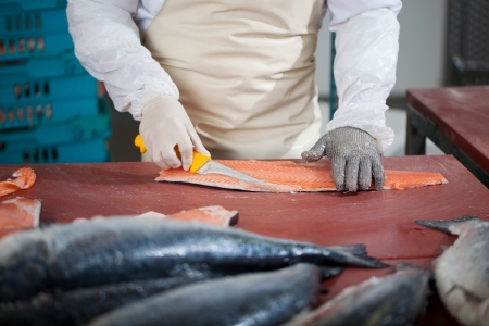 meat counter: Midsection of worker slicing fish at table