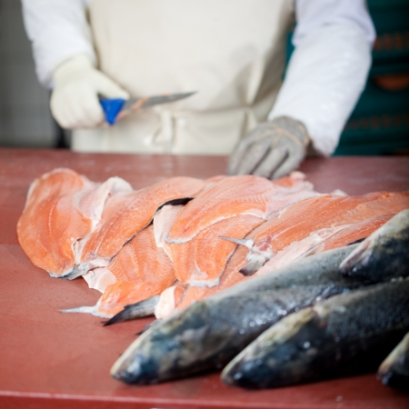 slicing: whole salmon and salmon fillets with worker in background Stock Photo