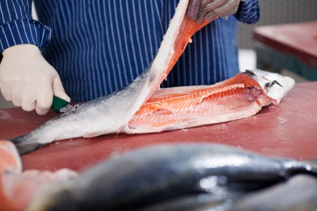 fish store: Midsection of worker cutting fish at table Stock Photo