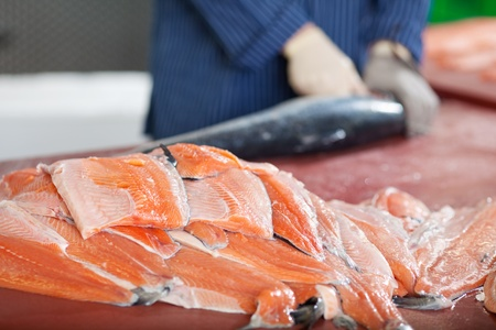 food processing: stacked salmon fillets lying with worker in background